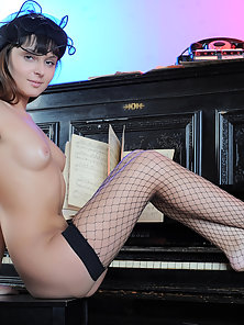 Sexy artist at work, black fishnet and posing on piano