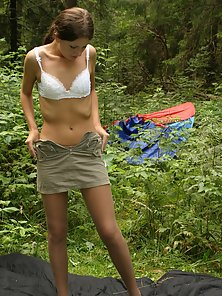 Amateur brunette is getting naked in woods