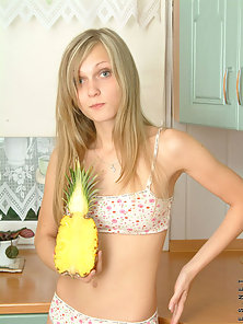 Cute and Lovely Kirsten Showing a Fruit in the Kitchen