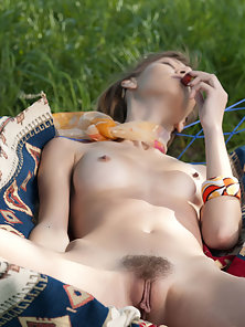 Lovely chick takes off her green dress and caresses pussy outdoor