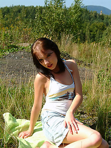 Skinny Brunette Babe Showing Her Sexy Naked Figure Sits In Outdoor Field
