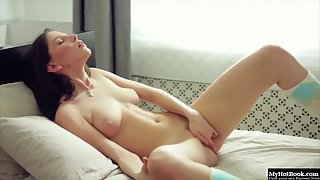 Hot brunette babe with big tits rubs her pussy